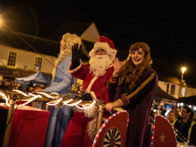 Children's Characters and Santa wave to crowds from Santa's Sleigh